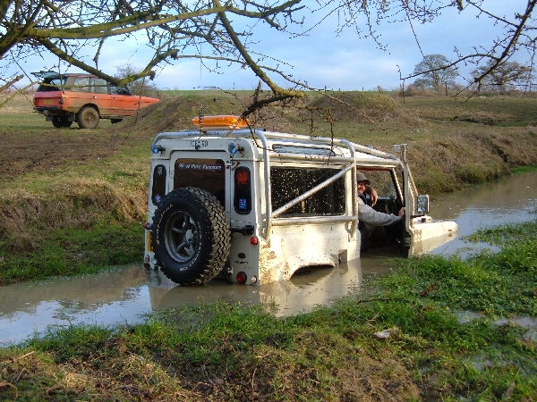 Once the event was over, Jon decided to go through the water splash, the plan was to wash the wheels, but this doesn't normally include the steering wheel! All was going well until he lost traction - so who is going to attach the rope? (Picture by Roger Taylor)